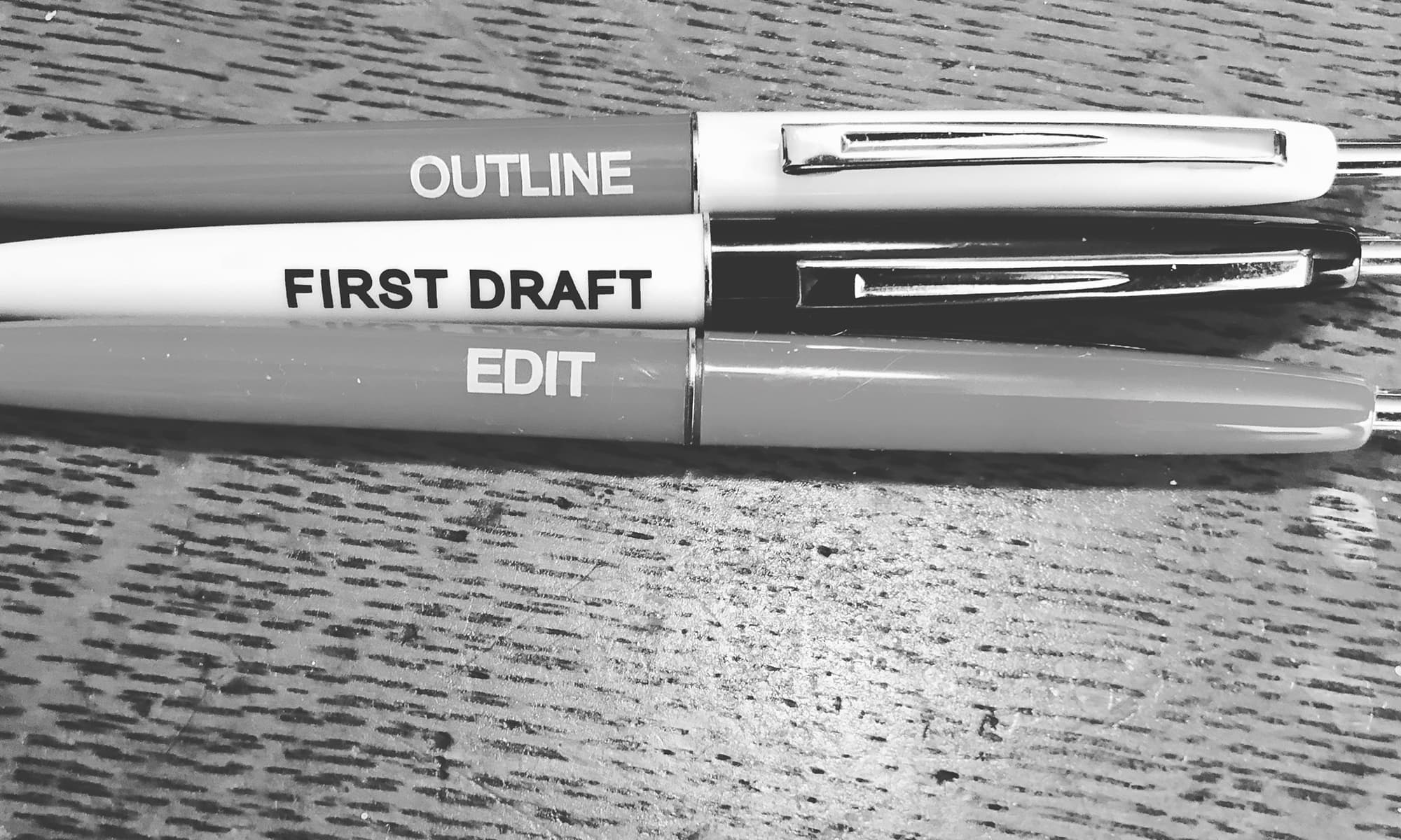 Three pens with the words Outline, First Draft, and Edit on them